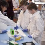 Two boys in lab coats participate in gram staining.