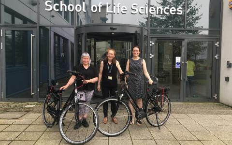Three people smiling in front of the School of Life Sciences with two electric bikes
